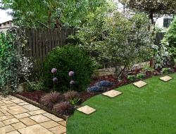 Kompozycja traw, czosnków ozdobnych i krzewów na tle kory sosnowej